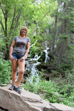 uterine fibroids | CU Rocky Mountain OB-GYN | patient Lisa poses by waterfall